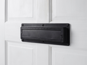 Closed black EcoFlap on a white door